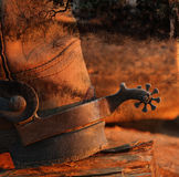 A cowboy boot and spur. The heel of a cowboy boot and spur in a grungy texture and a glowing sunset Stock Image