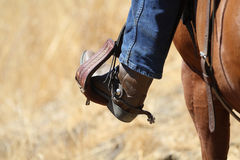 A cowboy boot. A cowboy boot, stirrup and spurs riding a horse royalty free stock photos