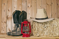 Cowboy Boots. Snake skin cowboy boots and hat on wood background with lantern royalty free stock images