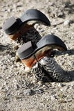 Cowboy boots buried in dirt. Vintage cowboy boots buried upside down in the dirt Stock Image