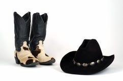 Cowboy Boots de peau de vache et chapeau noir avec le ruban de chapeau de Concho. Image stock