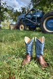 Cowboy boots and a Ford tracter. Blue cowboy boots in the grass with a blue tractor in the background stock photography