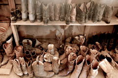 Cowboy Boots Galore. Tack Room full of  Well Worn Cowboy Boots Stock Photos
