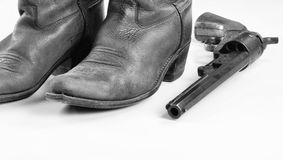 Cowboy boots and Guns. Old cowboy boots and  cowboy pistol in black and white with room for your type Royalty Free Stock Images