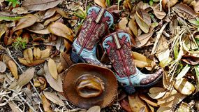 Cowboy boots and hat laying flat in a bed of leaves. Colorful blue and brown cowboy boots and hat lying in the center of a bed of leaves royalty free stock images
