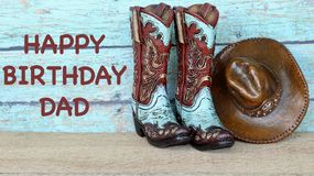 Cowboy boots and hat on a teal background. Teal and brown cowboy boots and hat standing on a wood table with happy birthday dad in brown text on a teal royalty free stock images