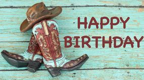 Cowboy boots and hat on a teal background. Teal and brown cowboy boots and hat standing on a wood table with happy birthday in brown text on a teal background stock photos