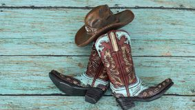 Cowboy boots and hat on a teal background. Colorful blue and brown cowboy boots and hat laying in the center of a teal background royalty free stock photo