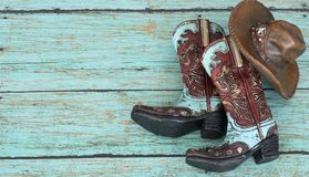 Cowboy boots and hat on a teal background. Colorful blue and brown cowboy boots and hat laying in the center of a teal background royalty free stock photos