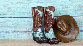 Cowboy boots and hat on a teal background. Pair of blue and brown cowboy boots and hat standing on a wooden and blue background with writing space royalty free stock photography