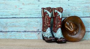 Cowboy boots and hat on a teal background. Pair of blue and brown cowboy boots and hat standing on a wooden and blue background with writing space stock photography