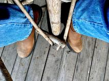 Cowboy boots and jeans. A perspective photo of someone wearing cowboy boots and jeans while sitting on a stool Stock Images