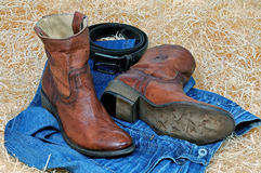Cowboy boots leather belt and blue jeans on straw. Pair of traditional brown leather cowboy boots and blue jeans and leather brown belt curtailed into a ring on stock photos