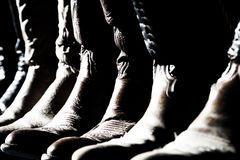 Cowboy Boots Lined Up. A row of cowboy boots lined up in high contrast sunlight and shadow (shallow focus point on middle of image royalty free stock images