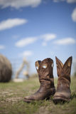 Cowboy boots in pasture. Pair of cowboy boots isolated in pasture in memory of deceased stock photography