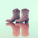Cowboy boots with reflection in wooden floor Stock Images