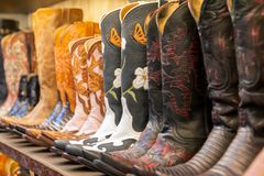 Cowboy boots on a shelf in a store aligned. Ornate boots, Texas royalty free stock images