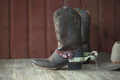 Cowboy boots, spurs and hat on old wood background. Cowboy boots with spurs and a hat on an old wood background royalty free stock photo