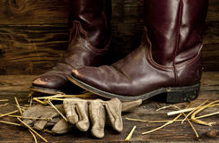 Cowboy boots on top of leather gloves. Royalty Free Stock Images