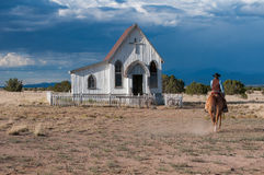 Cowboy in Brown Horse Going to White Wooden Church during Daytime Royalty Free Stock Photo