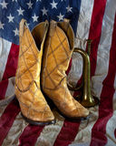 Cowboy Bugle. Cowboy boots and an old bugle with an American flag background Stock Photos