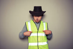 Cowboy builder wearing a high visibility vest and being rude Stock Photography