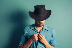 Cowboy buttoning his shirt. A young cowboy is standing by a blue wall and is buttoning his shirt Stock Image