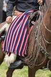 Cowboy a cavallo che porta poncio piegato sul rivestimento Immagini Stock