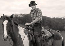 Cowboy a cavallo, equitazione con la camicia striata ed alberi nel fondo Fotografie Stock