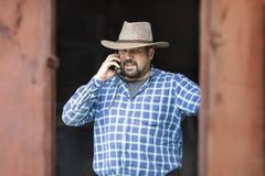 A cowboy with a cell phone in a hat and a beard stock photography