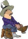 Cowboy che mette sui suoi caricamenti del sistema Fotografia Stock