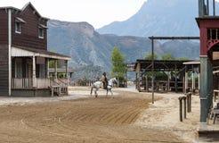 Cowboy che monta il suo cavallo nella città Fotografia Stock Libera da Diritti