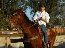 Cowboy che petting il suo cavallo Fotografia Stock
