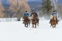 Cowboy che radunano i cavalli nella neve fotografie stock libere da diritti