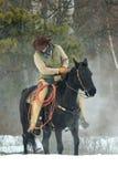 Cowboy checking is stirrups Royalty Free Stock Photo