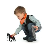 Cowboy child. With black horse toy Royalty Free Stock Image