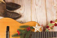 Cowboy christmas background with guitar and cowboy boots Stock Images