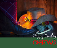 Cowboy Christmas card with holiday decorations. Cowboy Christmas card with holiday decorations and text.Greeting card with cowboy hat and shoe on wood Royalty Free Stock Photos