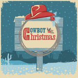 Cowboy christmas card with western hat and text on wood board Stock Images