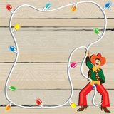 Cowboy Christmas Lasso Invitation. Cowboy with Christmas Lights Lasso against weathered wood Stock Photos