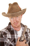 Cowboy close with gun smirk on face. A cowboy in his western hat holding on to his pistol royalty free stock image
