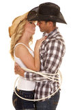 Cowboy couple rope around them ready to kiss Stock Images