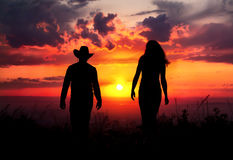 Cowboy couple silhouette at sunset. Young couple silhouette walking outdoors at sunset dramatic sky background. Man in cowboy hat and women nearby Royalty Free Stock Photo