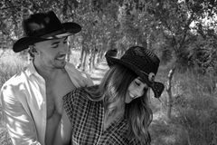 Cowboy and cowgirl couple with hats laughing and playing with each other stock photography