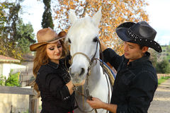 Cowboy and Cowgirl with horse. Cowboy and Cowgirl with a beautiful white horse Royalty Free Stock Photo