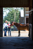 Cowboy, Cowgirl, and Horse - Vertical. A Cowgirl and Cowboy petting a brown horse outside a barn. Vertically framed photograph Royalty Free Stock Photos