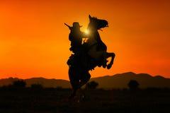 Cowboy de silhouette tenant l'arme à feu courte et montant un cheval photos stock