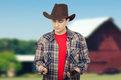 Cowboy deciding whom to call him Royalty Free Stock Image