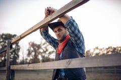 Cowboy in den Lederjacke- und Huthaltungen auf Ranch stockfoto