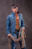 Cowboy in denim jacket with a rope. Stock Photos